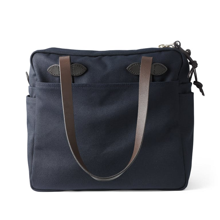 Discover the Filson Tote Bag with Zipper. An abrasion-resistant, water-repellent closable tote with a reinforced base and Bridle Leather handles.
