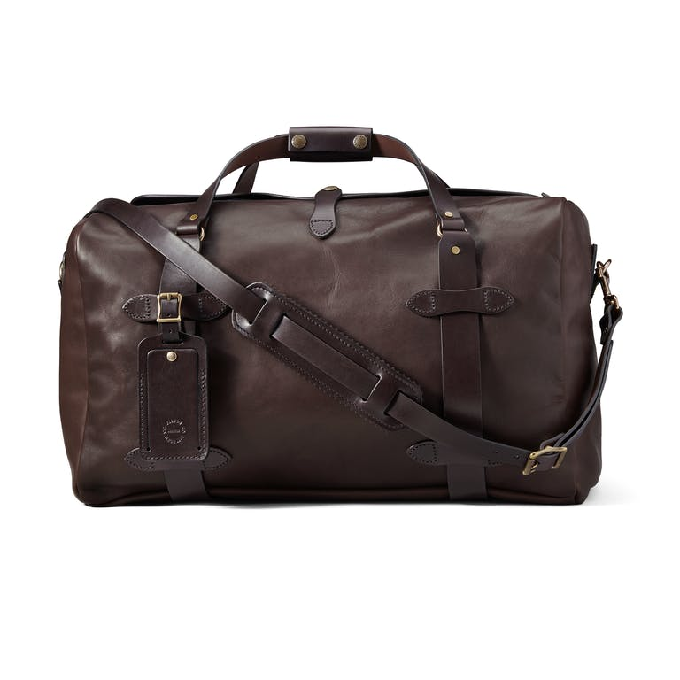 Discover the Filson Medium Weatherproof Leather Duffle, an overhead-friendly duffle bag, featuring Wickett & Craig Bridle Leather and brass hardware.